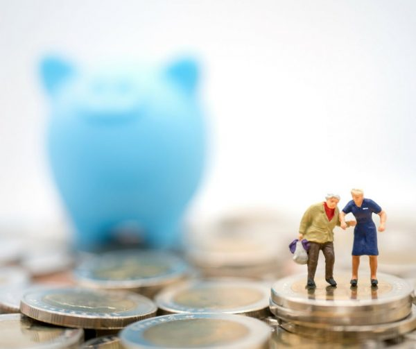 anziani si tengono per mano ed intorno a loro un salvadanaio ed i soldi